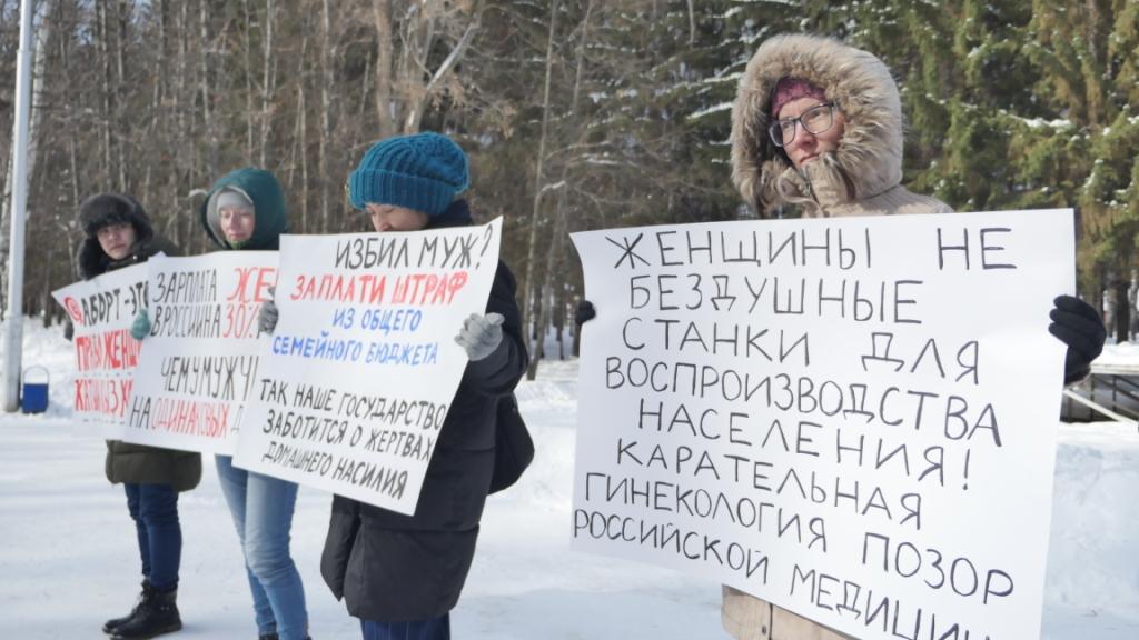 """8 марта: 8 женщин с плакатами в парке """"Волна"""""""